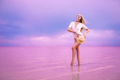 Incredible super model posing in pink lake. Beautiful young girl with a hat standing in a pink lake Stock Photo