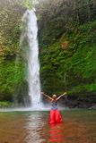 Woman stand in pool under waterfall, see on falling water royalty free stock image