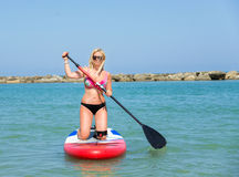 Woman on stand up paddle. Blonde woman on Stand Up Paddle Board, SUP,in blu sea Royalty Free Stock Images