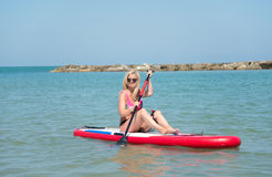 Woman on stand up paddle. Blonde woman on Stand Up Paddle Board, SUP,in blu sea Stock Images