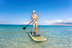 Woman stand up paddle board. S in tropical waters of hawaii Royalty Free Stock Photography