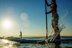 Woman on Stand Up Paddle Board. Women paddling stand up paddle board with sun and mountains in the background Stock Photos