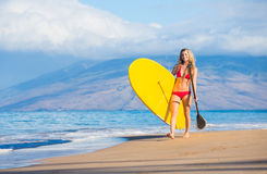 Woman with Stand Up Paddle Board. Attractive Woman with Stand Up Paddle Board, SUP, on the beach in Hawaii Royalty Free Stock Photography