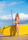 Woman with Stand Up Paddle Board. Attractive Woman with Stand Up Paddle Board, SUP, on the beach in Hawaii Royalty Free Stock Images