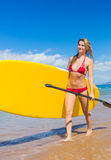 Woman with Stand Up Paddle Board. Attractive Woman with Stand Up Paddle Board, SUP, on the beach in Hawaii Royalty Free Stock Image