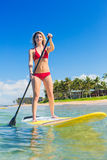 Woman on Stand Up Paddle Board. Attractive Woman on Stand Up Paddle Board, SUP, Tropical Blue Ocean, Hawaii Stock Photo