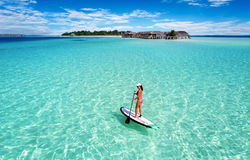 Woman on a Stand Up Paddle board over turquoise waters. Woman on a Stand Up Paddle board over turquoise, Maldivian waters Royalty Free Stock Photo