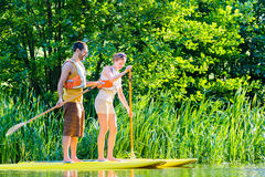 Woman with stand up paddle board sup on river. Friends paddling with surfboard sup on forest river stock photography