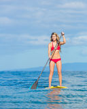 Woman on Stand Up Paddle Board. Young Attractive Woman on Stand Up Paddle Board, SUP, in the Blue Waters off Hawaii, Active Life Concept Royalty Free Stock Images