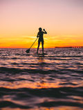 Woman stand up paddle boarding at dusk on a flat warm quiet sea with beautiful sunset colors Stock Image