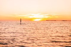Woman stand up paddle boarding on a quiet sea with beautiful sunset. Woman stand up paddle boarding on a quiet sea with sunset Stock Photos