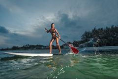 Woman stand up paddle boarding. At dusk on a flat warm quiet sea Stock Photos