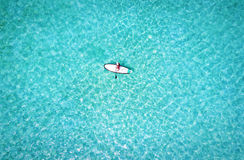 Woman on a stand up paddle boat over turquoise waters Royalty Free Stock Photo