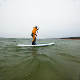 Woman on a stand up paddle. Woman stand up paddling in cold water on Baltic sea in Hanko, Finland Stock Images
