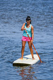 Woman stand up paddleboarding. On lake. Young girl doing watersport on lake. Female tourist in swimwear during summer vacation Stock Photography