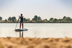 Woman stand up paddleboarding. On lake. Young girl doing watersport on lake. Female tourist in swimwear during summer vacation Stock Photos
