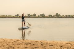 Woman stand up paddleboarding. On lake. Young girl doing watersport on lake. Female tourist in swimwear during summer vacation Royalty Free Stock Photography