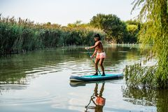 Woman stand up paddleboarding. On lake. Young girl doing watersport on lake. Female tourist in swimwear during summer vacation Stock Photo