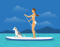 Woman Stand Up Paddling on Sap board with her Dog on a Sea Royalty Free Stock Image