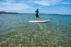 A woman stand up on a surfboard on the sea. royalty free stock image