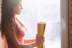 Woman stand by window hold yoga mat Stock Image