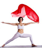 Woman stand in yoga asana and red flying fabric Stock Photography