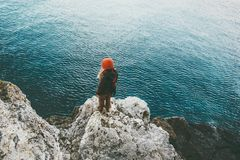 Woman standing above cold sea on cliff alone Travel Lifestyle concept outdoor. Solitude melancholy emotions Stock Images