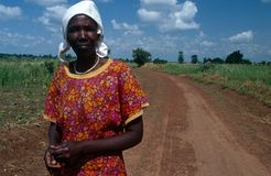 A woman standing against a stretch of dirt road, Uganda Royalty Free Stock Photography