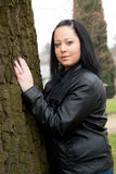Woman standing against a tree Royalty Free Stock Photos