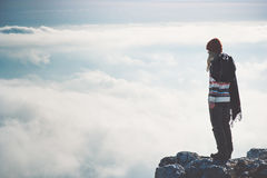 Woman standing alone on cliff over clouds landscape Royalty Free Stock Images