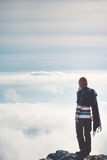 Woman standing alone on cliff over clouds Royalty Free Stock Photography