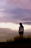Woman standing alone at the field during sunset Stock Photography