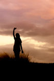 Woman standing alone at the field during sunset Royalty Free Stock Photography