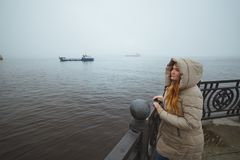 Woman standing alone at sea coast and looking on ship. Winter time. Seaman`s wife royalty free stock image