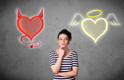 Woman standing between the angel and devil hearts. Pretty young woman standing and deciding between the angel and the devil heart stock photo