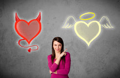 Woman standing between the angel and devil hearts Royalty Free Stock Photo