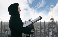Woman standing on Arc de Triomphe with binocular. Young woman standing on Arc de Triomphe with large pair of binoculars, Eiffel Tower Royalty Free Stock Images