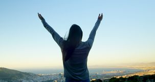 Woman standing with arms outstretched on top of the mountain 4k