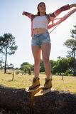 Woman standing with arms outstretched on a tree trunk Stock Photo