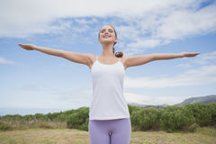 Woman standing with arms raised on countryside landscape Royalty Free Stock Photography