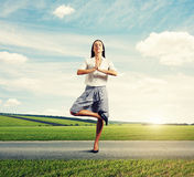 Woman standing in asana on the road Stock Photography