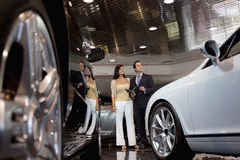 Woman standing with auto salesman in car showroom royalty free stock photos