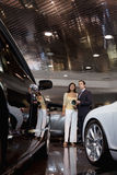Woman standing with auto salesman in showroom Stock Images