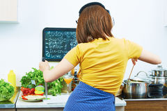 Woman standing back in kitchen, cooking healthy fo Stock Photos