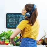 Woman standing back in kitchen, cooking healthy food with fun a