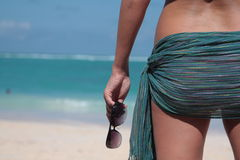 Woman standing back with tied pareo on the loins. With beach and ocean in background with sun glasses in hand Royalty Free Stock Image