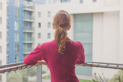 Woman standing on balcony of apartment Royalty Free Stock Photography