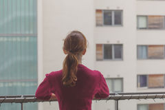 Woman standing on balcony of apartment Royalty Free Stock Photos