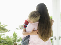 Woman standing on balcony, carrying son (5-7), boy with eyes closed, rear view stock images
