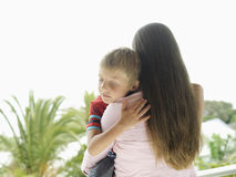 Woman standing on balcony, carrying son (5-7), boy with eyes closed, rear view stock photos